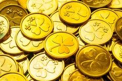 Fundo do dia do `s do St Patrick Moedas douradas com o trevo sob a luz do sol macia, conceito festivo do dia de St Patrick fotos de stock royalty free