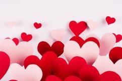Fundo do dia do Valentim Corações de papel vermelhos e cor-de-rosa do córrego da mosca para fora no contexto branco da cor Foto de Stock