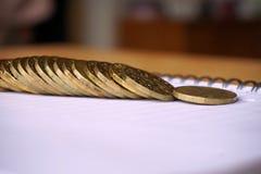 Fundo do dinheiro das pilhas do ouro de moedas e do metal da porca jovem no bloco de notas de papel Foto de Stock