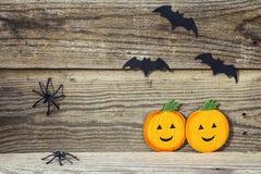 Fundo do feriado de Dia das Bruxas com dois abóboras, bastões e aranhas Foto de Stock Royalty Free
