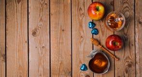 Fundo do feriado de Rosh Hashana com mel, maçãs e chocolate na tabela de madeira Vista de acima Imagem de Stock