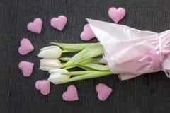 Fundo do feriado do dia de Valentim ou do dia das mulheres com o ramalhete das tulipas frescas decoradas com corações cor-de-rosa Imagens de Stock