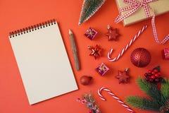 Fundo do feriado do Natal com caderno e decorações na tabela vermelha fotografia de stock