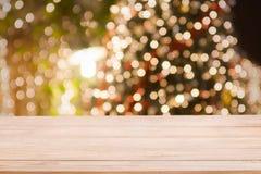 Fundo do feriado do Natal com tampo da mesa de madeira vazio sobre a luz festiva do bokeh imagem de stock