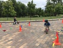 Fundo do grunge da independência Day Entretenimento no parque da cidade Bicicletas do passeio das crianças sem pedais, 'trotinett Foto de Stock Royalty Free