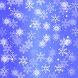 Fundo do inverno com flocos de neve em um fundo azul Fotografia de Stock
