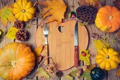 Fundo do jantar da ação de graças com placa da forma do coração Folhas da abóbora e da queda de outono na tabela de madeira Imagens de Stock
