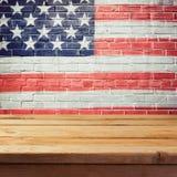 Fundo do Memorial Day com a tabela de madeira vazia e a bandeira dos EUA Imagem de Stock
