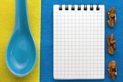 Fundo do menu Cozinheiro Book Bloco de notas da receita com nozes em um fundo azul e amarelo Fotos de Stock Royalty Free