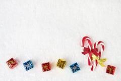 Fundo do Natal Bastão de doces decorado com fita e os presentes pequenos no fundo branco da neve Copie o espaço Fotografia de Stock