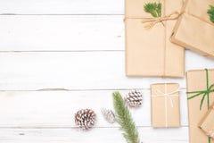 Fundo do Natal com as caixas de presente atuais feitos a mão e decoração rústica na placa de madeira branca Foto de Stock