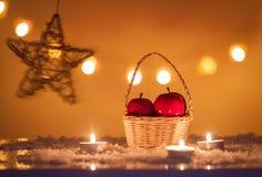 Fundo do Natal com a cesta com maçãs, velas, neve, as estrelas e luzes vermelhas do bokeh Imagem de Stock Royalty Free