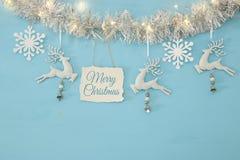 Fundo do Natal com a festão festiva da árvore, os cervos brancos, e os flocos de neve brancos de papel sobre a luz - fundo azul Fotos de Stock