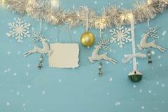 Fundo do Natal com a festão festiva da árvore, os cervos brancos, e os flocos de neve brancos de papel sobre a luz - fundo azul Fotografia de Stock Royalty Free