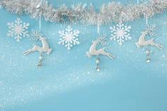Fundo do Natal com a festão festiva da árvore, os cervos brancos, e os flocos de neve brancos de papel sobre a luz - fundo azul Foto de Stock Royalty Free