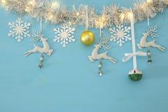 Fundo do Natal com a festão festiva da árvore, os cervos brancos, e os flocos de neve brancos de papel sobre a luz - fundo azul Imagem de Stock