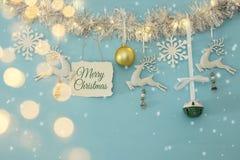 Fundo do Natal com a festão festiva da árvore, os cervos brancos, e os flocos de neve brancos de papel sobre a luz - fundo azul Fotografia de Stock
