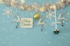 Fundo do Natal com a festão festiva da árvore, os cervos brancos, e os flocos de neve brancos de papel sobre a luz - fundo azul Foto de Stock
