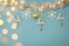Fundo do Natal com a festão festiva da árvore, os cervos brancos, e os flocos de neve brancos de papel sobre a luz - fundo azul Imagens de Stock Royalty Free