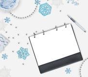 Fundo do Natal com lugar para o texto Flocos de neve azuis, grânulos brilhantes, caderno e pena no fundo branco Plano para o nex Imagens de Stock