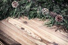 Fundo do Natal com os cones do pinheiro e do pinho no fundo de madeira Fotografia de Stock Royalty Free