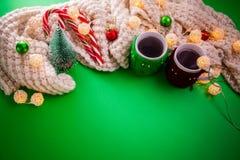 Fundo do Natal com os copos do chá, dos bastões de doces e do lenço cercados com uma festão no fundo verde Foto de Stock Royalty Free