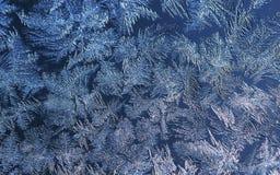 Fundo do Natal com teste padrão gelado no vidro do inverno iluminado pela luz solar imagens de stock