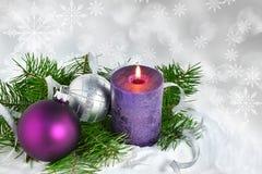 Fundo do Natal com vela e decorações Bolas roxas e de prata do Natal sobre ramos de árvore do abeto na neve Fotografia de Stock