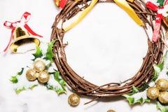 Fundo do Natal, grinalda tecida do ramo da videira com sinos dourados e folha verde com bola dourada Fotografia de Stock Royalty Free