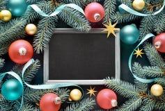 Fundo do Natal na madeira com quadro-negro, galhos do abeto, colorfu Fotos de Stock