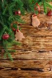 Fundo do Natal O abeto ramifica, as bolas vermelhas, pão-de-espécie nas placas marrons idosas Estilo rústico Copie o espaço Imagem de Stock Royalty Free
