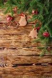 Fundo do Natal O abeto ramifica, as bolas vermelhas, pão-de-espécie nas placas marrons idosas Estilo rústico Copie o espaço Imagem de Stock