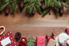 Fundo do Natal O abeto ramifica com os cones na tabela de madeira com livro, bola, presentes, pirulito Imagens de Stock Royalty Free