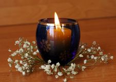 Fundo do Natal ou do ano novo vela ardente no vidro azul, fotos de stock royalty free