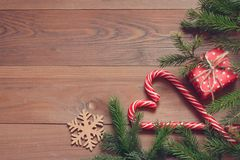 Fundo do Natal Pirulitos vermelhos e brancos, caixa de presente, flocos de neve de madeira e ramos de árvore do abeto na tabela d Imagem de Stock Royalty Free