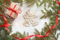 Fundo do Natal Quadro verde dos ramos de árvore no fundo de madeira branco, caixa de presente com a fita vermelha do cetim, sinos imagem de stock royalty free