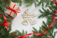 Fundo do Natal Quadro verde dos ramos de árvore no fundo de madeira branco, caixa de presente com a fita vermelha do cetim, sinos imagens de stock royalty free