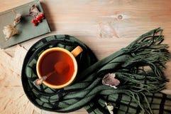 Fundo do outono - copo do chá, do livro velho e do lenço morno no fundo de madeira Do outono vida ainda Imagem de Stock Royalty Free