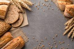 Fundo do pão com trigo, pão estaladiço aromático com grões, espaço da cópia, vista superior Brown e da grão dos nacos vida inteir fotografia de stock