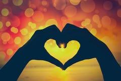 Fundo do Valentim Silhueta da mão humana na forma do coração sh Foto de Stock