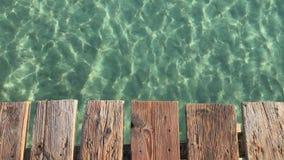 Fundo do verão, placas de madeira velhas cais e água do mar com reflexões do sol filme