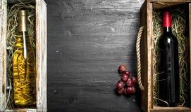 Fundo do vinho Garrafas do vinho vermelho e branco em umas caixas Fotos de Stock Royalty Free