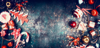 Fundo do vintage do Natal com doces e as decorações vermelhas do feriado: Chapéu de Santa, árvore, estrela, bolas, vista superior