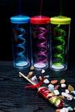 fundo dos doces com as garrafas da cor no fundo preto de madeira Imagens de Stock Royalty Free