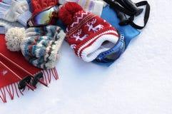 Fundo dos esportes de inverno com roupa do esqui e equipamento, espaço branco da cópia da neve Fotografia de Stock Royalty Free