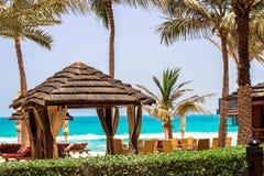 Fundo dos feriados das férias Pavilhão e sunbeds em coas do oceano imagens de stock royalty free