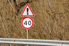 Fundo dos sinais de estrada do perigo dos arbustos adiante e limite de velocidade 40 Imagens de Stock