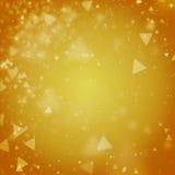 Fundo dourado abstrato com luzes defocused do bokeh do triângulo Foto de Stock