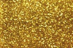 Fundo dourado borrado com luzes efervescentes do círculo Bokeh glittery amarelo brilhante da festão do Natal Contexto escuro imagem de stock
