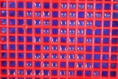 Fundo e textura azuis vermelhos com gotas de água fotografia de stock
